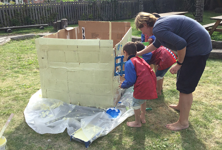 Børn og pædagog maler Lille Madsens hus